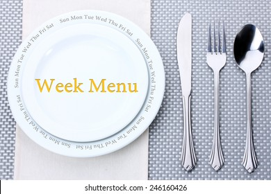 """Plate with text """"Week Menu"""", fork, knife and spoon on tablecloth background"""