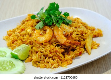 A plate of Thai style food, fried rice with sour and spicy tom yum flavor with prawns served with  sliced lemon and fresh cucumber topped with coriander