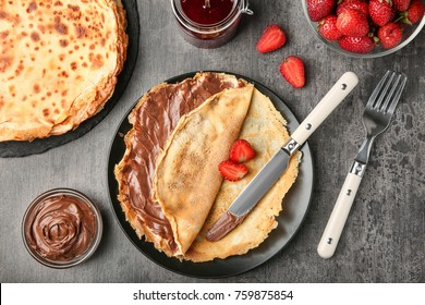 Plate with thin pancakes with chocolate paste and berries on table
