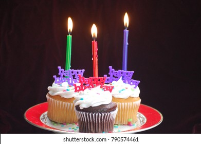 Plate of three cupcakes with lit candles and happy birthday signs.