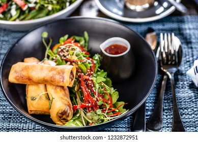 A plate of three spring rolls, salad and red chilli sauce