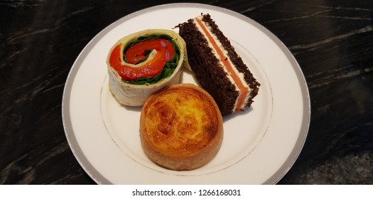 A plate with three types of appetizers: pita bread roulade with capsicum/red pepper and spinach, rye bread with cream cheese and smoked salmon, and a ham quiche lorraine