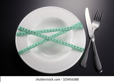 Plate tied with green tape measure with fork and knife