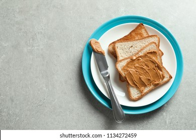 Plate with toast bread and peanut butter on table, top view