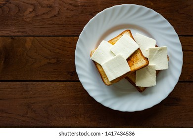 Plate with toasted bread with cheese isolated on wooden background, top view