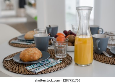 Plate with toasted bread and glass of juice on grey background, top view