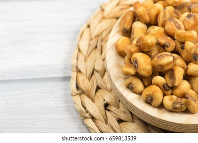 Plate with toasted corn on wooden background.