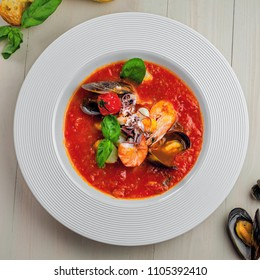 Plate of tomato seafood soup on a rustic wooden table. Tasty Italian classic meal. Top view shot.