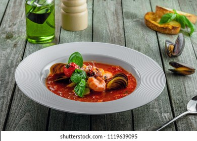 Plate of tomato seafood soup on a rustic wooden table. Tasty Italian classic meal.