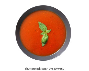 plate of tomato soup with basil isolated on a white background, top view