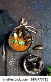 Plate of tomato soup with mussels and Basil on a wooden cutting Board. A bowl of mussels and sea salt and pepper on the Board. Dark blue textured background. Top view.