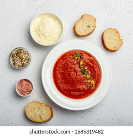 Plate of tomato soup served with cheese and bread
