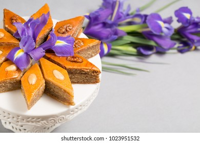 Plate of traditional Azerbaijan baked pastry dessert pakhlava baklava with walnuts and honey for Novruz holiday spring celebration with bouquet of purple flowers fleur de lis on light grey background