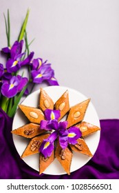 Plate of traditional Azerbaijan baked pastry dessert pakhlava baklava with walnuts for lilac Novruz holiday spring celebration with bouquet of purple flowers fleur de lis on light grey background