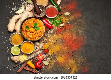 Plate of Traditional Chicken Curry and set of spices on dark concrete background