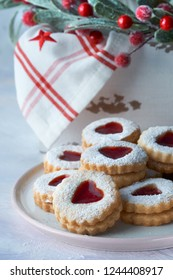 Plate of traditional Christmas Linzer cookies filled with strawberry jam on white table with Xmas decorations in green and red