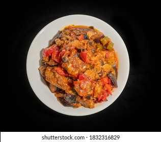 Plate of traditional Egyptian Moussaka plate on a black background. Vegetarian dish consists of velvety eggplant stew with capsicum, garlic, onions, tomato and dried mint.