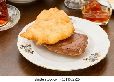 Plate of traditional fried dough, Turkish pisi halka, or fried dough crumpets, served on an old white dish at wood table with chocolate spread on top. Copy space for text area, angle view.