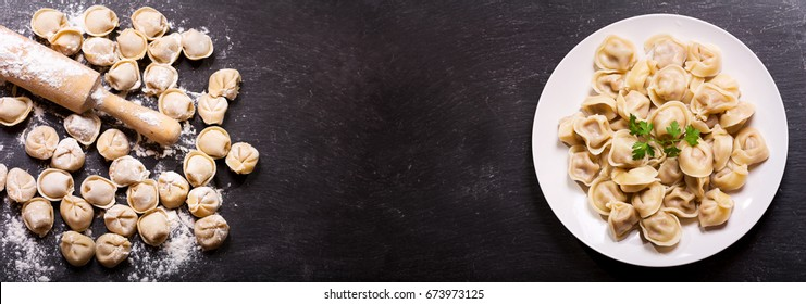 Plate of traditional russian pelmeni, ravioli or dumplings on black background, top view