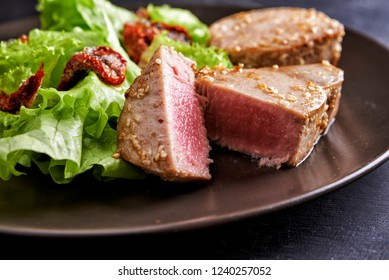 plate of tuna staek with salad