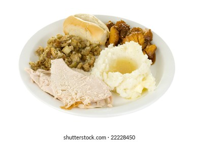 A plate of turkey, mashed potatoes and gravy, stuffing, sweet candied yams and a roll.