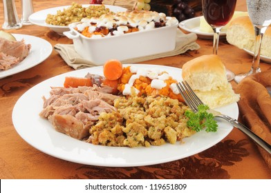 A plate of turkey pot roast with carrots, dressing and sweet potatoes
