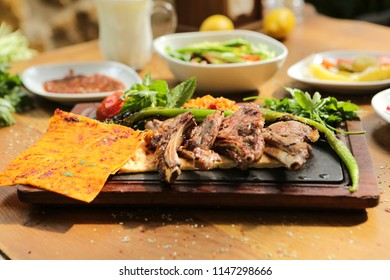 A plate of Turkish style grilled lamb chops (Pirzola) served withed grilled tomatoes red peppers on wood