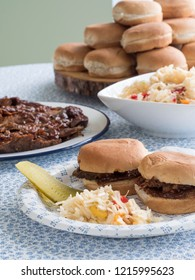 A plate of two beef brisket sandwiches on buns, accompanied by coleslaw and pickle, in front of the platter of beef slices, bowl of slaw and stack of buns