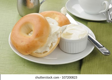 A plate with two sliced bagels with cream cheese