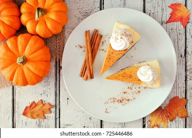 Plate with two slices of pumpkin cheesecake with whipped cream, overhead view on a white wood background