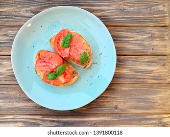 A plate with two tomato toasts topped with fresh basil. Top view, eating healthy. Home made recipe. Easy seasonal meal. Snack or appetizer.Sprinkled with coarse sea salt. Horizontal, rustic style.