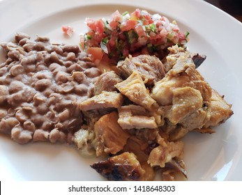 plate with typical food of the State of Michoacan, minced pork for tacos, mexican sauce and refried beans