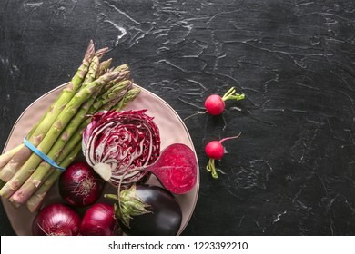 Plate with various fresh vegetables on dark table