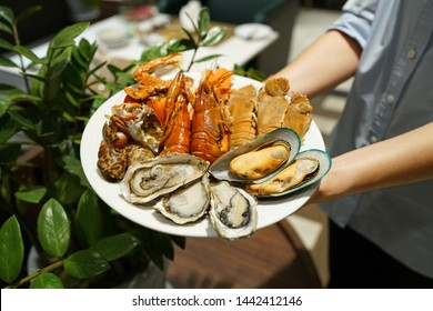 Plate of various types of seafood set, steamed rock lobster, baby lobster, New Zealand mussel, blue crab and fresh pacific oyster, Dinner buffet seafood night.