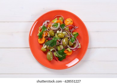 plate of vegetable salad with pickled green olives on white wooden background