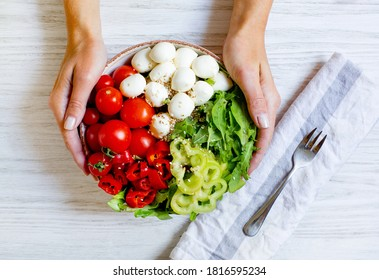 plate with vegetables tomatoes pepper arugula cheese mazzarella in female hands on a white wooden table top view