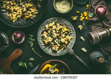 Plate with vegetarian tortellini pasta with vegetables, herbs and mushrooms on dark rustic kitchen table background with ingredients and utensils, top view