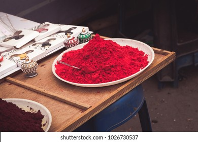 A plate of vermillion red powder with small colourful Indian Traditional Rajasthani Sindhoor Boxes in Guruvayur street,India