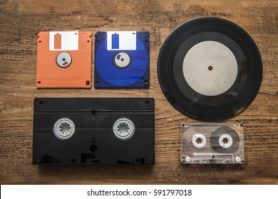 plate, Videocassette, compact audio cassette and floppy disk. Retro storage devices. Outdated technology concept. on wooden table background.