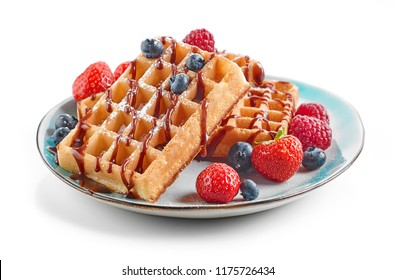 plate of waffles decorated with chocolat sauce and fresh berries isolated on white background
