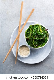 Plate with wakame salad, sesame and chopsticks