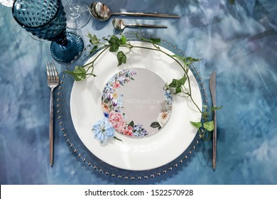 A plate with a wedding day sign, on a table with a blue tablecloth, a knife, a fork and flowers. A stylized wedding dinner. Wedding Scenery.