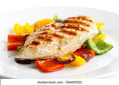 Plate of whole seasoned grilled chicken breast on roasted peppers.