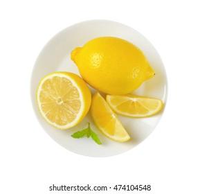 plate of whole and sliced lemons