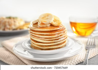 Plate with yummy banana pancakes on kitchen table
