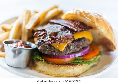 A plated bacon burger and french fries