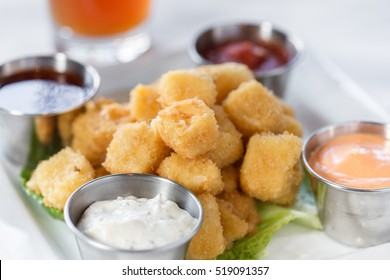 A plated dish of fried cheese curds and dipping sauces