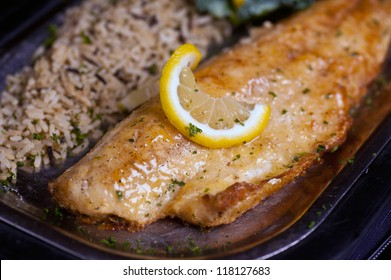 Plated Walleye Fish With Lemon Peel And Rice Pilaf