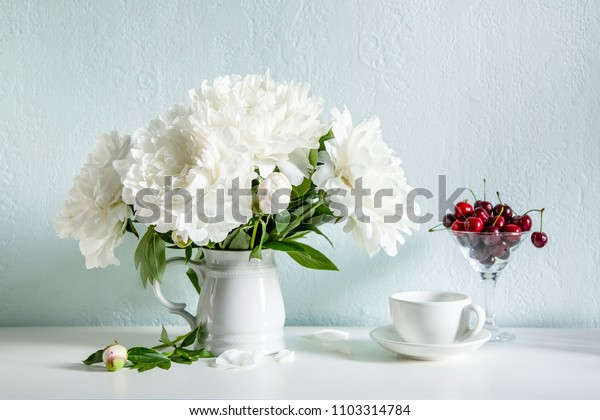 Plateful of cherry and bouquet of flowers