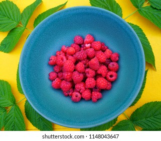 Plateful of fresh Finnish raspberries served on blue plate on yellow table with green raspberry leafs for decoration.